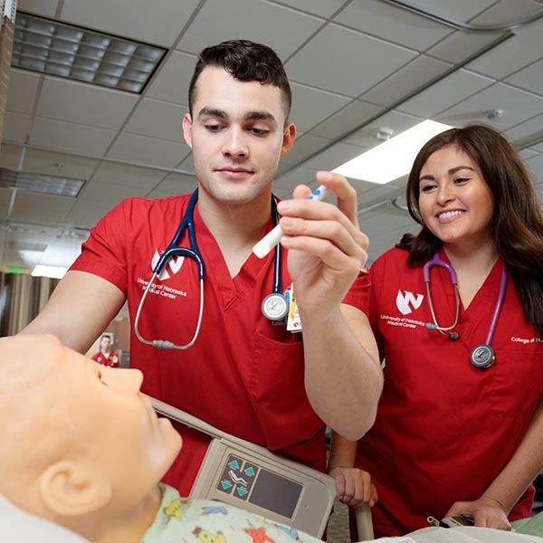 Nursing students work with a simulator