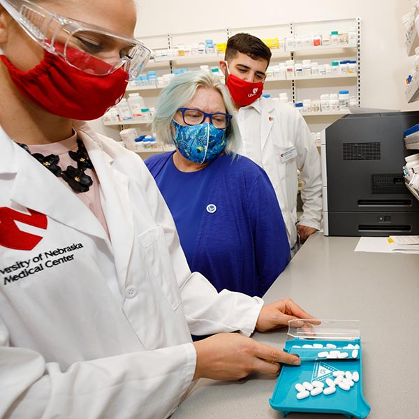 Pharmacy students and faculty in a simulated pharmacy