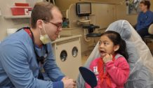 Ingrid Gonzales, 6, shows third-year dental student Jon Isaacson her teeth at the annual UNMC College of Dentistry Children's Dental Day on Feb. 2. (Photo by Margaret Cain.)